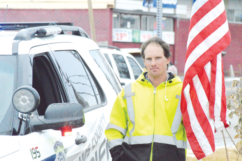 Thornton resident Michael Kapaun brought his American flag to the site of an alleged Jan. 24 shooting to honor local police. Adams County Deputy Sheriff Heath Gumm died in the shooting, and Kapaun said he wanted to honor all first responders.