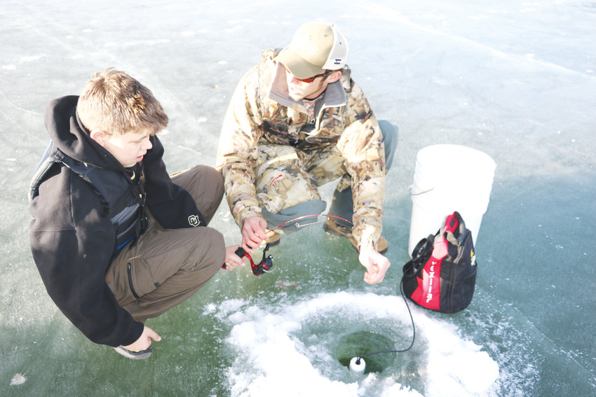 Austin Parr, manager of Discount Fishing Tackle, shows a student at Bear Creek Lake Park how to ice fish during its 101 class on Jan. 20.