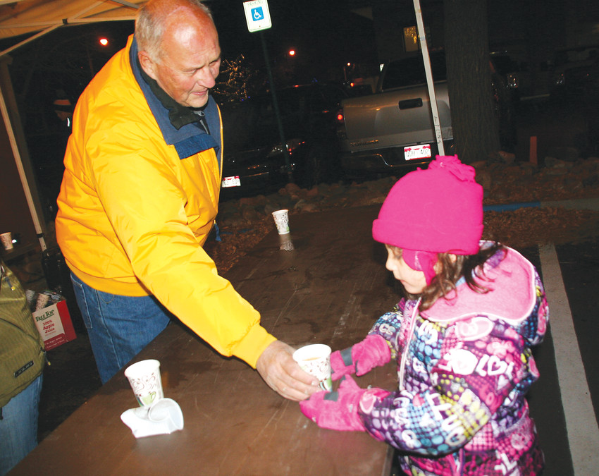 Golden Lion Judd Dickey hands a cup of warm cider to Braelyn Matlock, 6, in the parking lot of the Golden Visitors Center after the 2016 Candlelight Walk. The Lions provide and serve the cider for free, and it is something Candlelight Walk attendees look forward to each year.