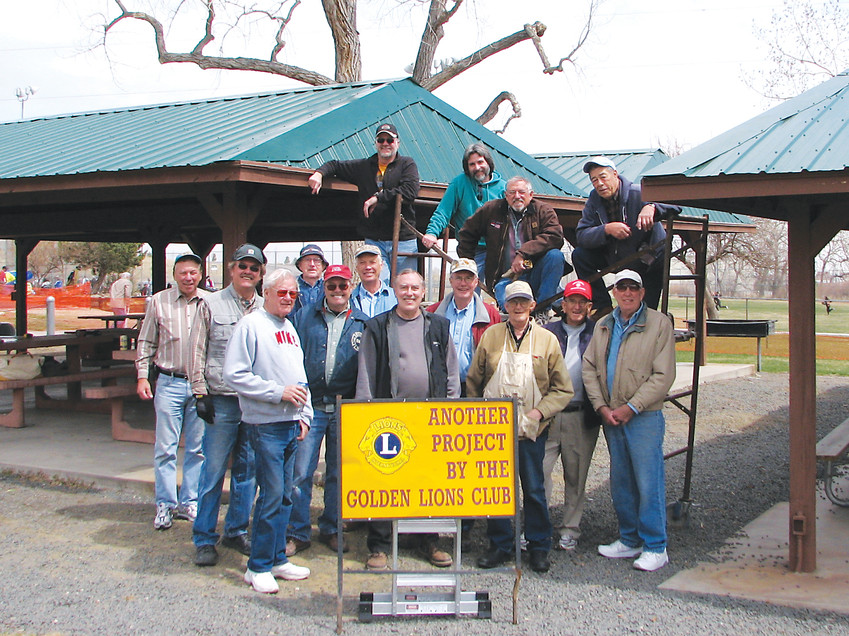 The Golden Lions Club celebrates the completion of re-roofing project at Grampsas park, 4471 Salvia St. in Golden, in 2009. For this project, Lions members removed the wood shingles on four of the park's pavilions and put on new steel roofing.