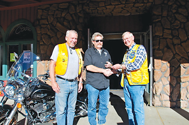 Kevin Desloover of Arvada, center, shakes hands with Golden Lions Club members from left, Ken Park and club president Peter Keppler Oct. 29, 2016, after winning a new 2016 Harley-Davidson Road King motorcycle. The Golden Lions Club put on the motorcycle drawing biannually. Proceeds from the ticket sales benefit the Golden Lions Club's Community Betterment Fund.