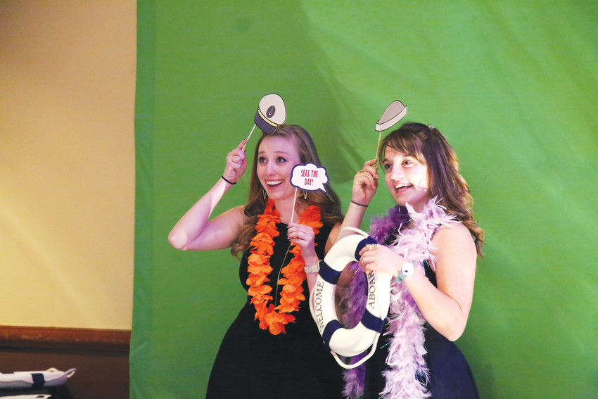 Rebecca Mettler and Sara Fulmer pose with props at the photobooth at the 93rd annual Arvada Chamber of Commerce Awards Dinner.
