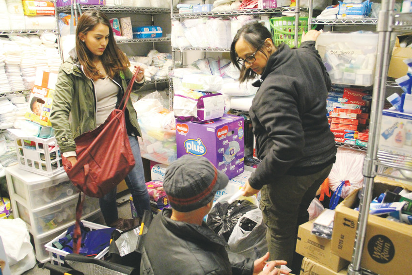 From left: Sara Cardona, 21, an intern with House of Hope; Chiles Freidman, 59, a volunteer with the organization; and Reneé Struck, 33, also an intern, collect another round of supplies at House of Hope to give out to homeless people during surveying for the Point-in-Time count. The three volunteers partnered with leader Patric Hughes on Jan. 29 as one of the several groups that administered the survey in the Denver metro area.