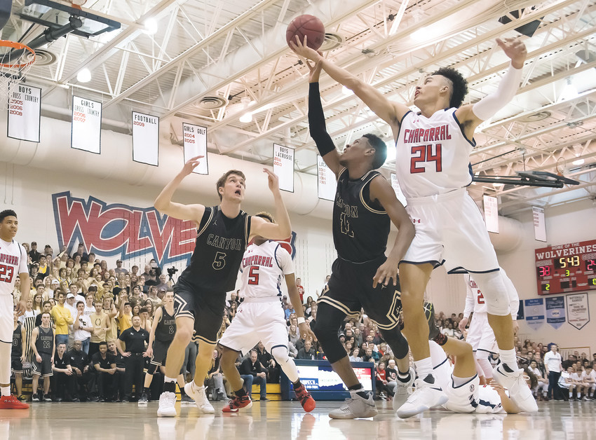 Chaparral's Bryce Matthews (24) tries to hang on to the loose ball as Rock Canyon's Tyson Gilbert also gets a hand in there as teammate Sam Masten (5) looks ready to grab the ball if it comes his way.  The Wolverines defeated top-ranked Rock Canyon 73-57 Feb. 2 in Parker.