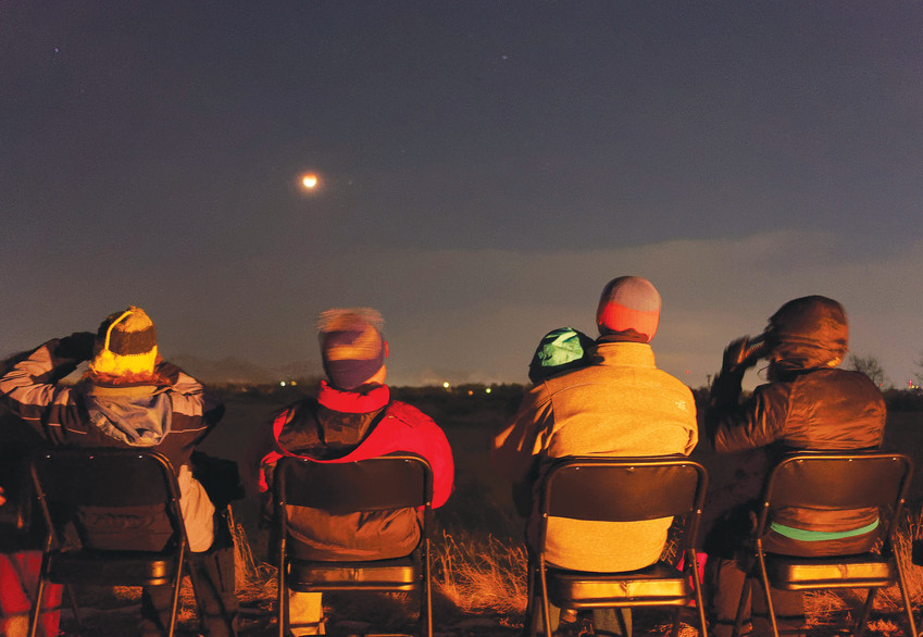 Spectators watch as the moon is subsumed behind the earth's shadow.