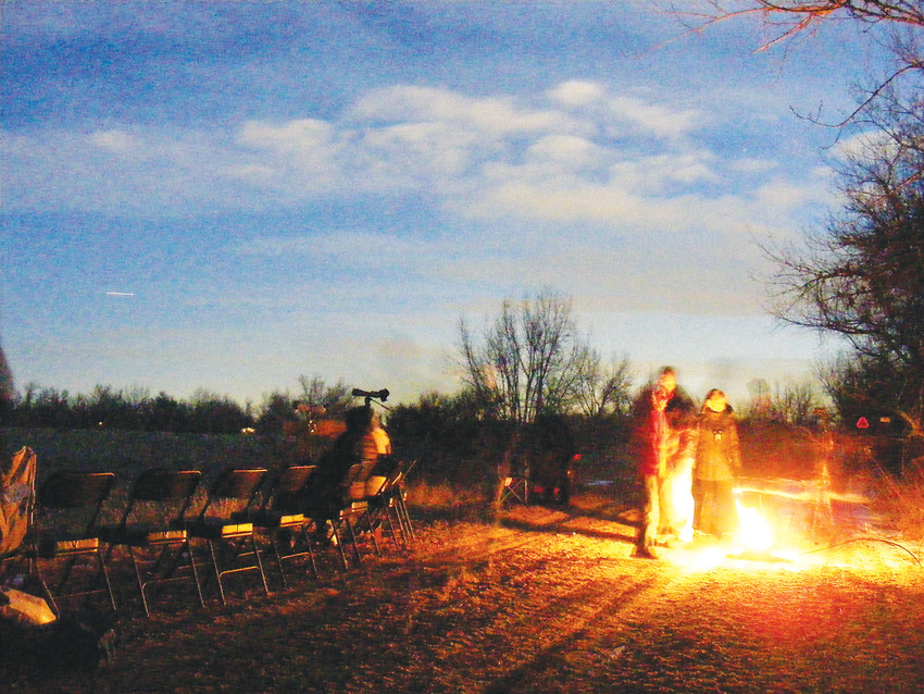 Astronomy fans peer into the cosmos by Cooley Lake while others warm themselves by a fire.