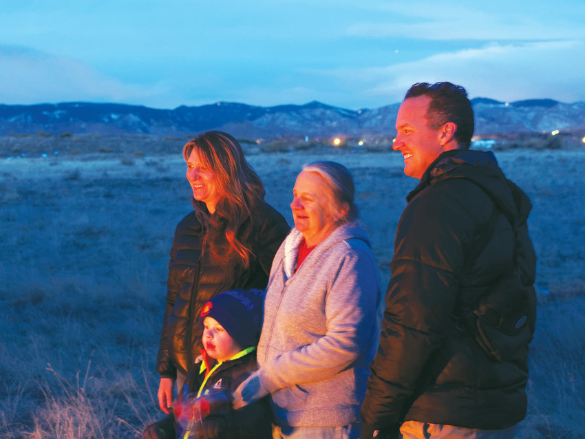Christine Schlegel, left, son Blake McRea, 4, Carolyn Albertson and South Platte Park Manager Skot Latona warm themselves by the fire as the eclipse fades into clouds in the west.