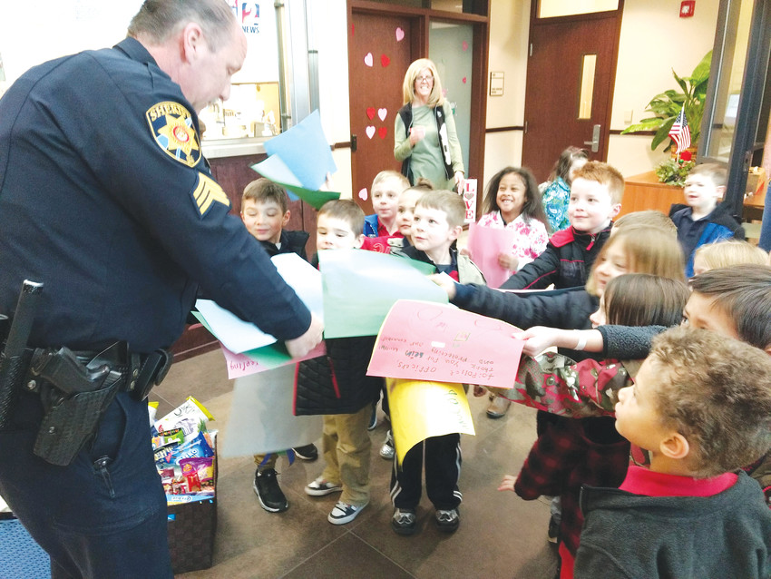 Pre-K and kindergarten students from Primrose School at Highlands Ranch Business give handmade cards to a Douglas County deputy. The kids traveled to the sheriff's office on Jan. 30 to show support following two officer-involved tragedies in Douglas and Adams counties.