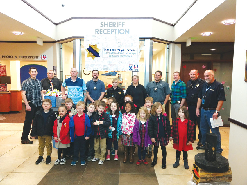 Pre-K and kindergarten students from Primrose School at Highlands Ranch Business Park stand with deputies and staff of the Douglas County Sheriff's Office after delivering cards and snacks on Jan. 30.