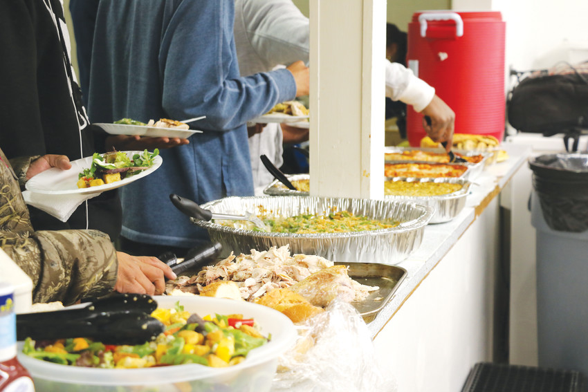 Homeless families at Mean Street Ministry's shelter serve themselves dinner during the evening of Jan. 29. The shelter is open to families in need of a place to stay from December through April.