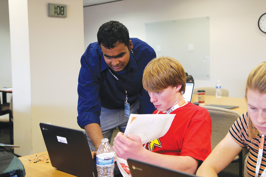 Akshay Sankaran, with Cisco, assists Green Mountain High student Caleb Neel during a break out session.