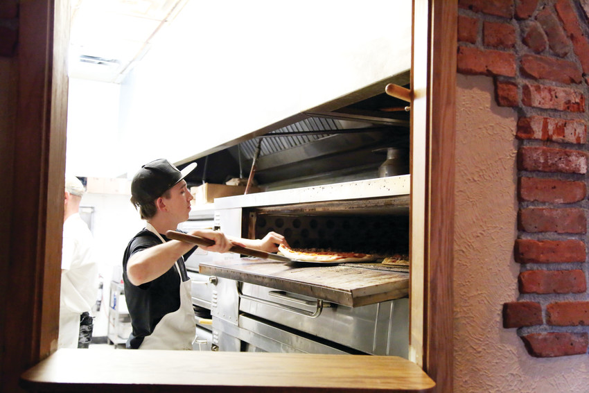 Bailey Piper mans the pizza oven on a Friday night at Randi's Pizza last year.