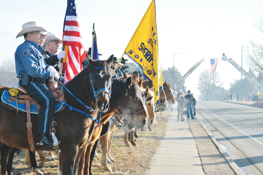 Members of the Colorado State Sheriff's Posse Association, mounted police officers from across the state, wait at attention for the funeral procession for Adams County Deputy Heath Gumm to pass Feb. 2 along South Boulder Road in Lafayette.
