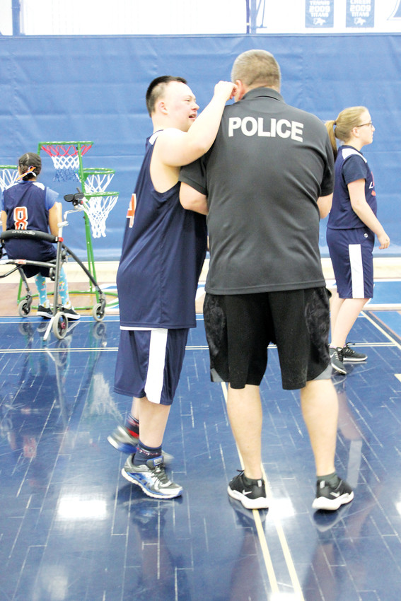 "Legend Unified basketball player Justin ""Knucklehead"" Kulinski tries to psych out opposing team member Officer Dan Britton before the Legend Unified vs. Parker Police Department game."