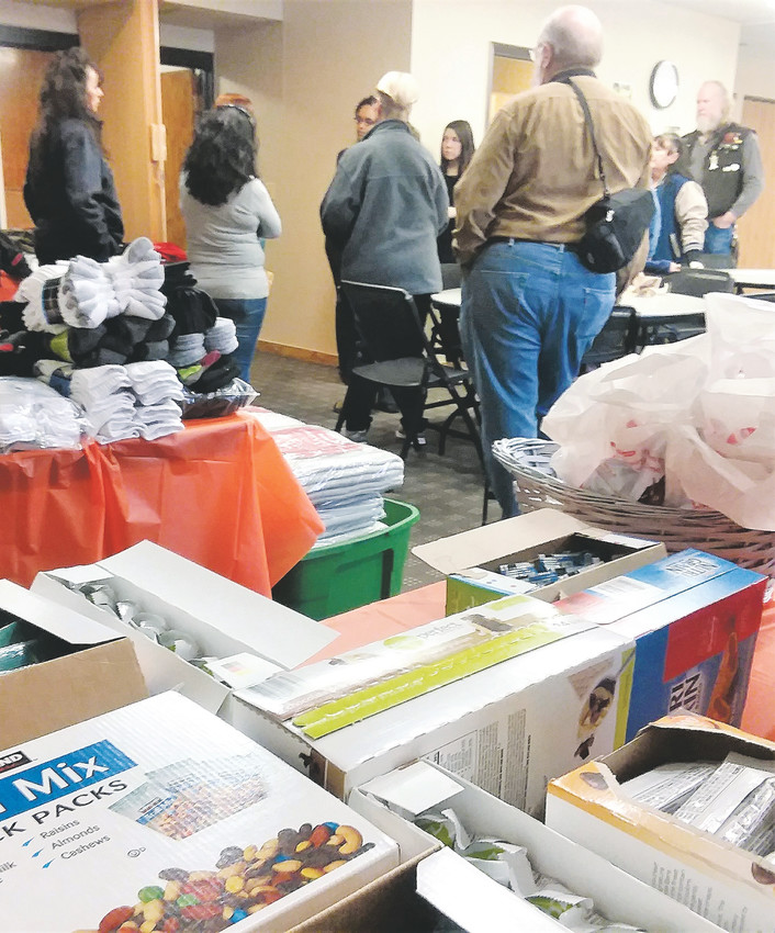 Volunteers talk in a room full of donated goods for homeless individuals Jan. 29 at Westminster's 72nd Avenue Swim and Fitness Center as Everyone Counts magnet program kicks off.