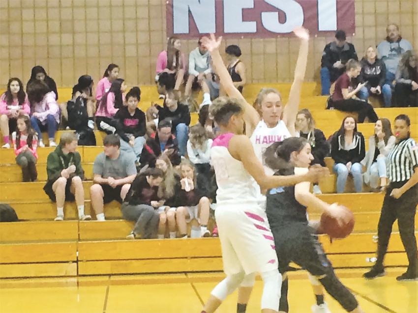 Horizon's Izzy Allen (left) and Sam Deem trap Mountain Range's Lillian West near the half court line in the fourth quarter during the Jan/ 30 game.