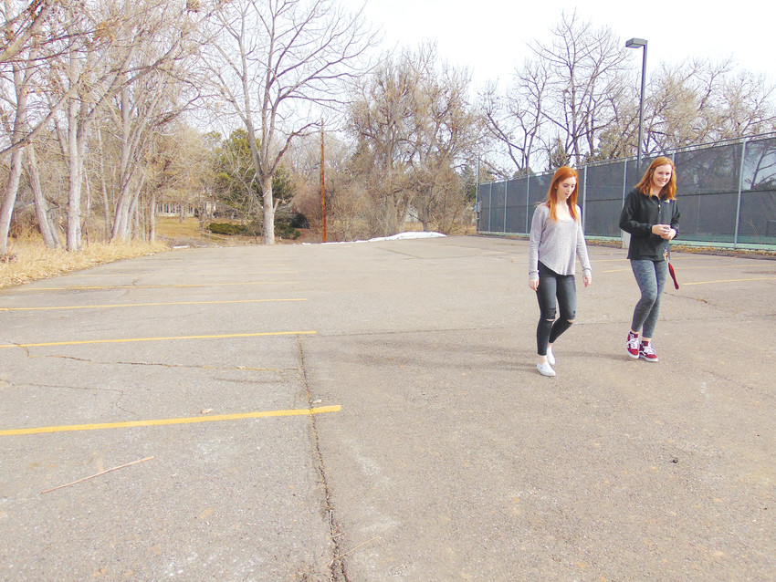 Heritage High School seniors Sarah Ervin, left, and Alexa Balkema walk across the parking lot they'd like to see turned into a hockey rink.