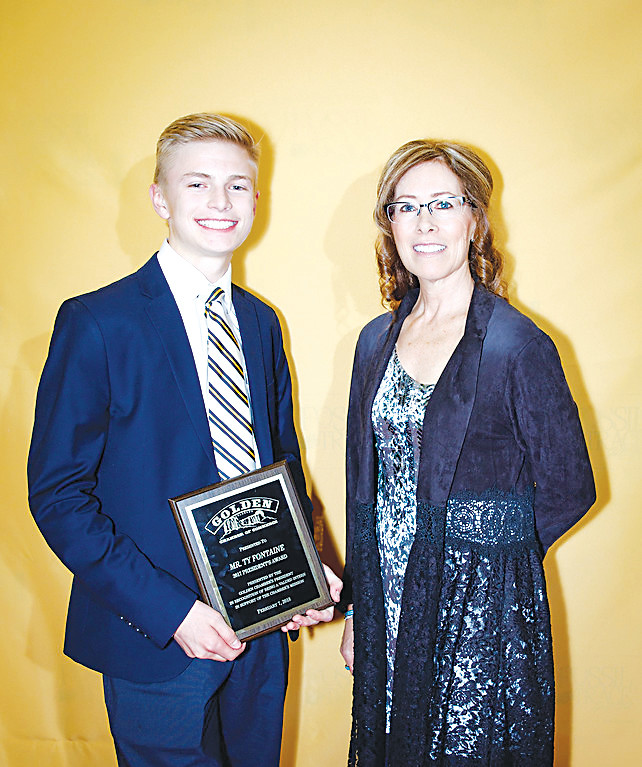 Ty Fontaine, left, a student at D'Evelyn Junior/Senior High School who did an internship with the Golden Chamber of Commerce, gets his picture taken with Leslie Klane, the chamber's CEO and president, after receiving the President's Award at the chamber's annual awards dinner on Feb. 7.