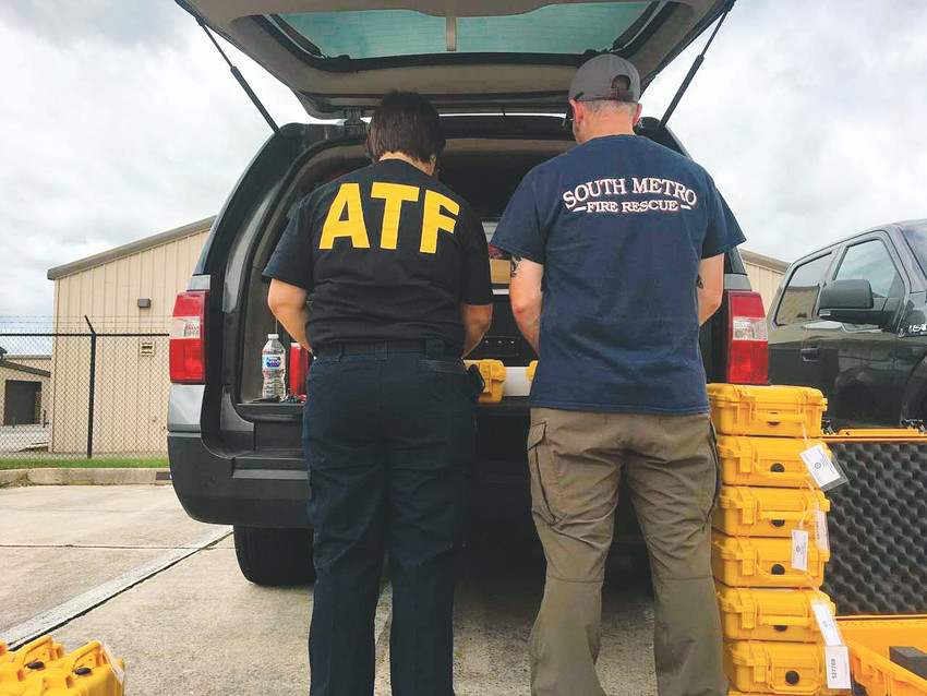 South Metro Fire Rescue's Eric Hurst works alongside the ATF to check satellite phones before giving them to law enforcement officers headed to Florida for Hurricane Irma.