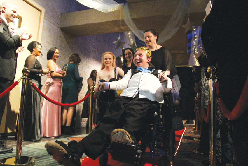 Guests with special needs and volunteers come down the red carpet at the Night to Shine event at the Hilton Denver Inverness hotel Feb. 9. More than 400 people — guests, volunteers and parents — turned out for the event.