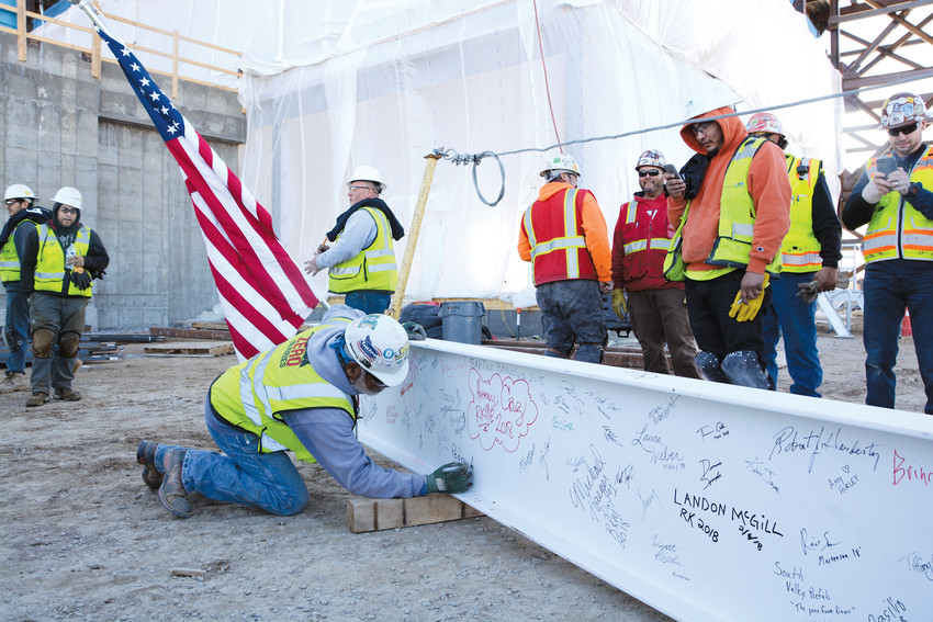 Construction crews working on the future UCHealth Highlands Ranch Hospital in the Central Park development, east of Lucent Boulevard and north of Town Center, sign their names on a metal beam adorned with a traditional pine tree and the American flag. The beam was raised and installed on one of the tallest spots of the hospital on Feb. 6.