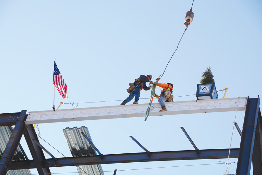 Mortenson Construction employees working on the future UCHealth Highlands Ranch Hospital in the Central Park development install a metal beam adorned with a pine tree and the American flag on one of the tallest spots of the structure on Feb. 6.