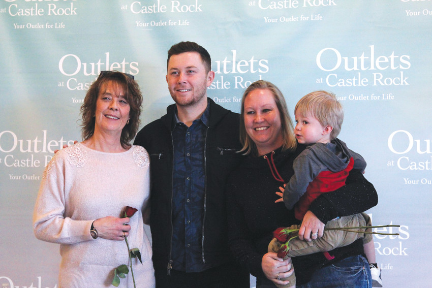 Jackie Herrington, her daughter, Katie McClain, and grandson Gavin pose for a photo with Scotty McCreery.