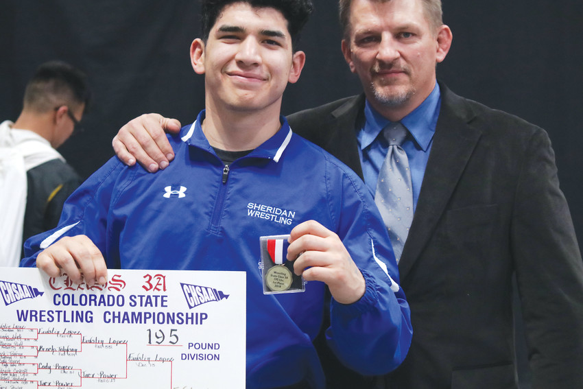 Sheridan's Faustin Lopez is joined by his coach Monte Nitchie as the wrestler holds his medal and the bracket he received for winning the Class 3A 195-pound championship at the state wrestling tournament held Feb. 15-17 at the Pepsi Center in Denver.