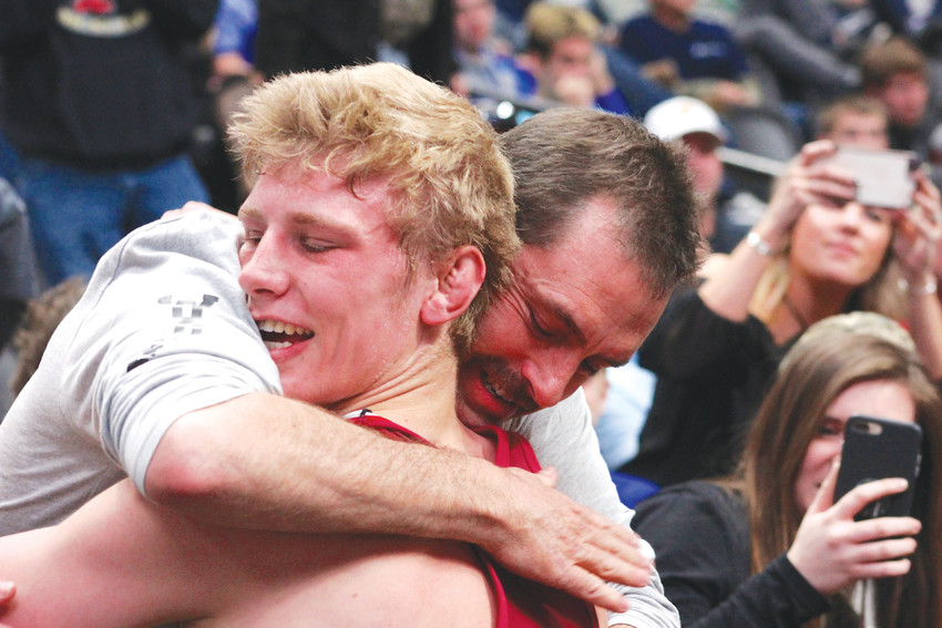 Senior Jayden Woodruff of Ponderosa hugs his father, John, after winning the 195-pound title Feb. 17 at the State Wrestling Championships at the Pepsi Center. Woodruff defeated Alec Hargreaves of Rocky Mountain, 7-0, in the title match and finished the season with a 46-6 record.
