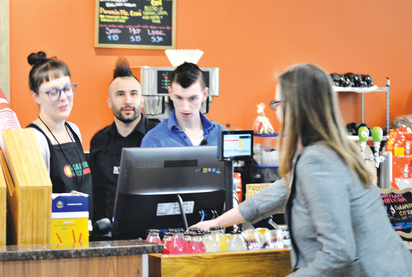 Westminster City Councilor Anita Seitz buys a cup of coffee at the newly opened coffee bar in the Local Foods Market, 72nd and Sheridan Boulevard on Saturday, Feb. 18.