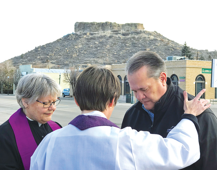 Rev. Janet Fullmer and Rev. Julie McNitt pray with Rod Walker during the Ashes to Go event on Feb. 14 at the corner of Fourth and Wilcox Streets in Castle Rock.