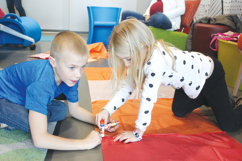Brother and sister Gavyn and Kai Moots, both 7, team up during the Slick Science program at the Douglas County Libraries' Lone Tree branch to build a homemade hot air balloon.