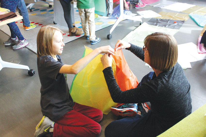 Jenna Blinci, 9, gets help building a hot-air balloon from Carol Schlueter, patron services technician at the Douglas County Libraries' Lone Tree branch, during the Slick Science program.