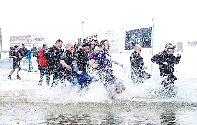 Members of the Lone Tree Police Department rush into the Aurora Reservoir during the annual Aurora Reservoir Polar Plunge to benefit Special Olympics Colorado.