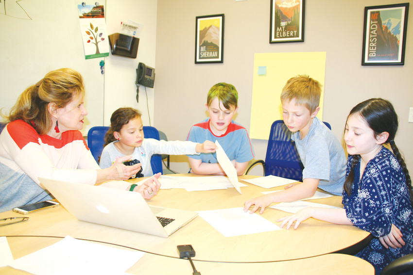 Artist Susan Cooper shows Mitchell Elementary School third-graders, from left, Addy Brown, Rowan Goble, Seamus Wisell and Jacey Thompson her initial design work, based on the students' artwork, for a sculpture that will be displayed in the school's atrium.