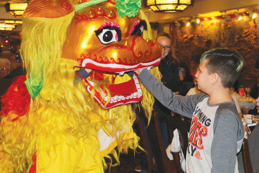 "Diego Jaramillo ""feeds"" a red gift envelop to one of the lion dance teams during the Chinese New Year celebration at the Twin Dragon restaurant in Englewood. The 10-year-old said the lion dancers were cool. This is the 41st year the restaurant has held a two-day Chinese New Year celebration complete with lion dancers."