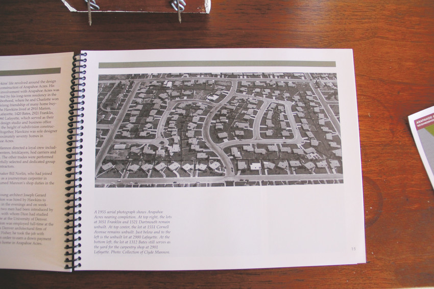 A 1955 photo showing an aerial view of the Arapahoe Acres neighborhood, looking eastward, in a book on its history by Diane Wray Tomasso. The book sits on a table at the house at 1420 E. Cornell Ave., part of a tour of homes Feb. 24 organized with involvement by the Thrive Real Estate Group, 20th Century Interiors, the Leak Finder Roofing Company and the Englewood Historic Preservation Society. The neighborhood is bounded by East Dartmouth Avenue, South Marion Street, East Bates Avenue and South Franklin Street.