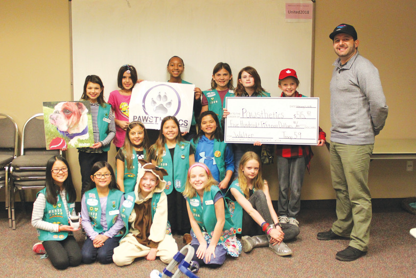Justin Finesilver, owner of Pawsthetics, receives a check from Lone Tree Girl Scout Troop 59, to help pay for a prosthetic leg and paw for Walter, a rescue dog in Connecticut.