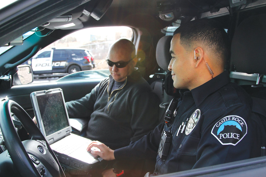 Troy Thompson, a clinician, left, and Marcos Whyte, a Castle Rock police officer, sit in their patrol car while on duty Feb. 16 as part of the Community Response Team. The team responds to mental health calls as part of a unique program seeking to keep people with mental illness out of jail and the emergency room, but also to provide follow-up care.