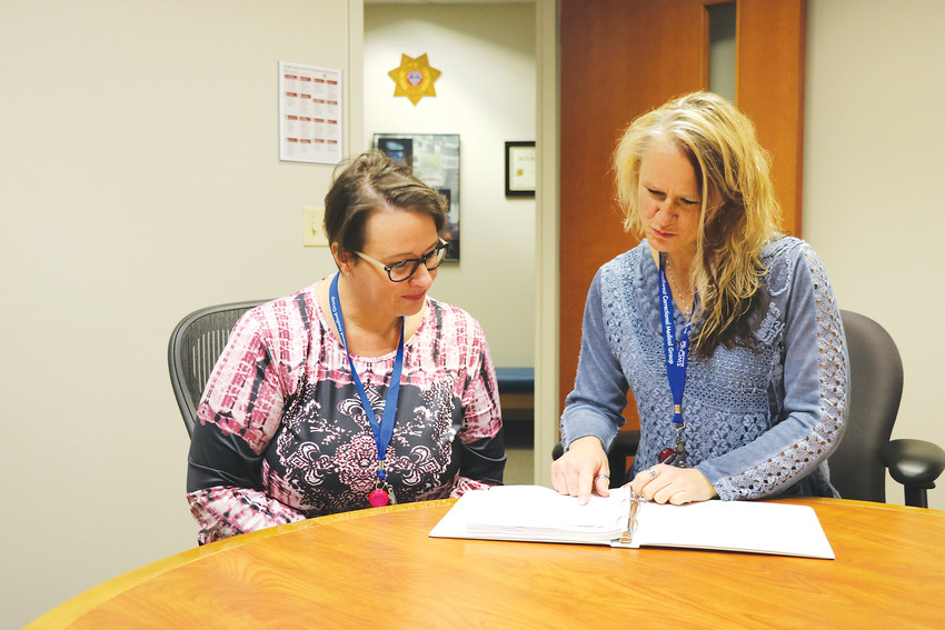 "Shauna Shipps, left, licensed professional mental health clinician, and Jennifer Glenn, health services administrator, review paperwork at the Douglas County Justice Center. The two work in the jail, which in recent years has seen an overwhelming number of inmates with mental illness. ""There are just no resources,"" Glenn said. ""You have mentally ill people on the streets, not taking their medication, and then they commit a crime."""