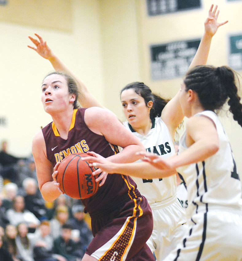 Golden senior Makena Prey, left, drives past a pair of D'Evelyn defenders during the opening half Feb. 27 at D'Evelyn Junior/Senior High School. The Demons defeated the Jaguars for the third time this season to advance to the Great 8 of the Class 4A girls basketball state tournament.
