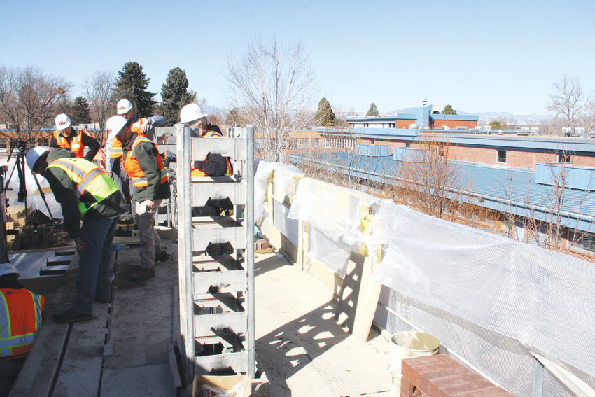 Construction workers stand during the brick-laying process at Clayton Elementary Feb. 27. The view overlooks the current Clayton building in the background.