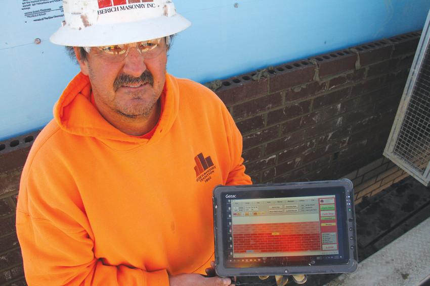 "Rodney Strouse, a fifth-generation brick-layer, stands with a tablet showing the progress of SAM — for ""semi-automated mason"" — in laying bricks for the new building at Clayton Elementary School in Englewood Feb. 27. Working on Clayton is the SAM100's first construction project in Colorado."