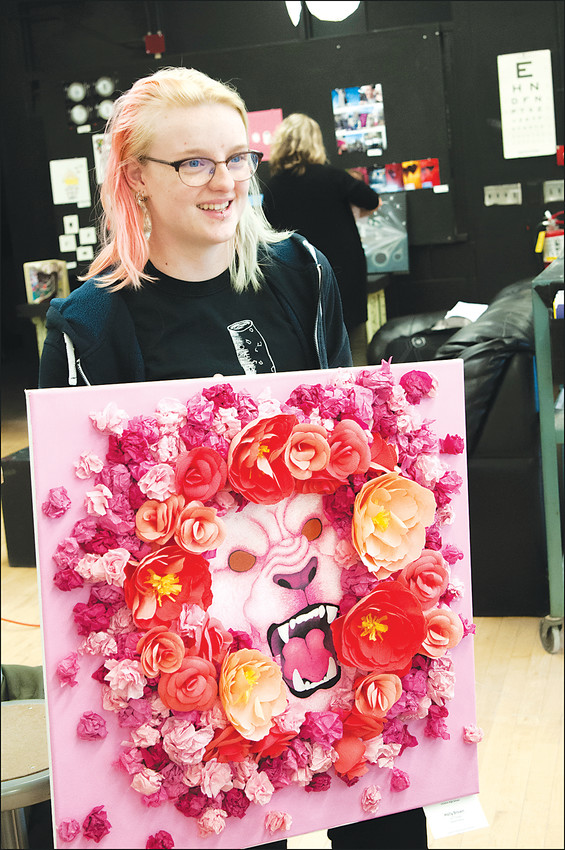 Littleton High School art student Holley Brown presents her three-dimensional piece, a flower-decorated Lion mask (the lion is LHS mascot). She is very much interested in theater arts as well.
