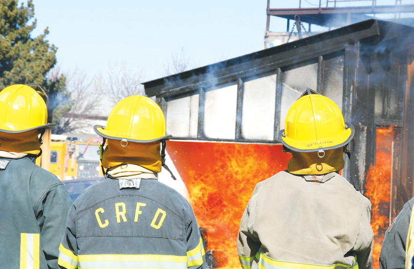 Firefighter recruits watch as a structure burns on March 2 as part of a training exercise at the West Metro Training Center in Lakewood. The training included building three small structures that each replicate different construction types commonly found in the community, then burning them to learn about fire behavior.