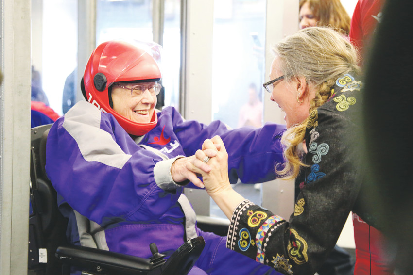 Trudy Goldman is greeted with excitement after her skydive experience by Amy Fogarty, activities coordinator at Brookdale Senior Living.