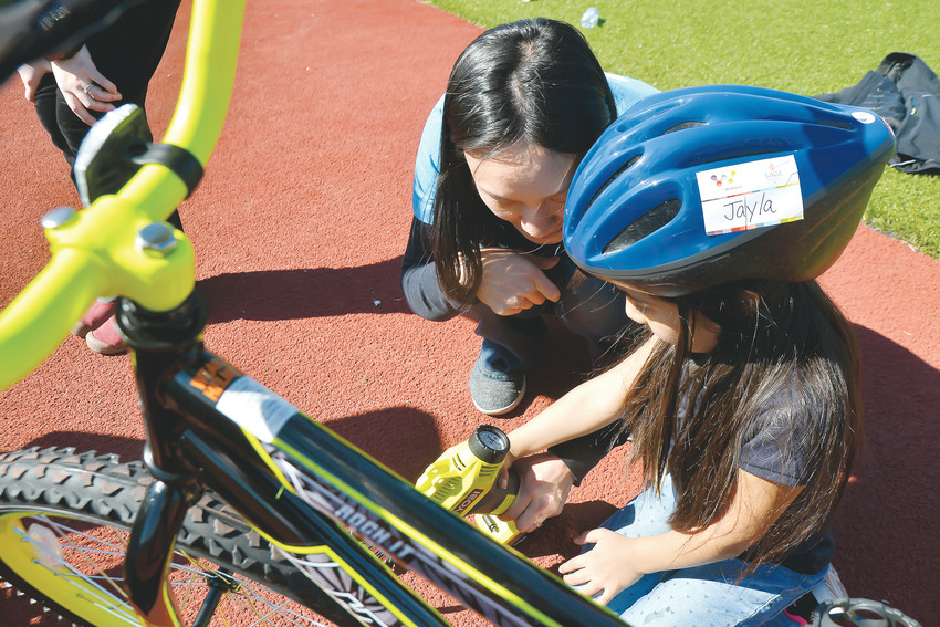 Thornton Elementary School kindergarten student Jayla helps tighten a bolt on her new bicycle. She was one of 75 students to receive new bikes March 1 at a special event.