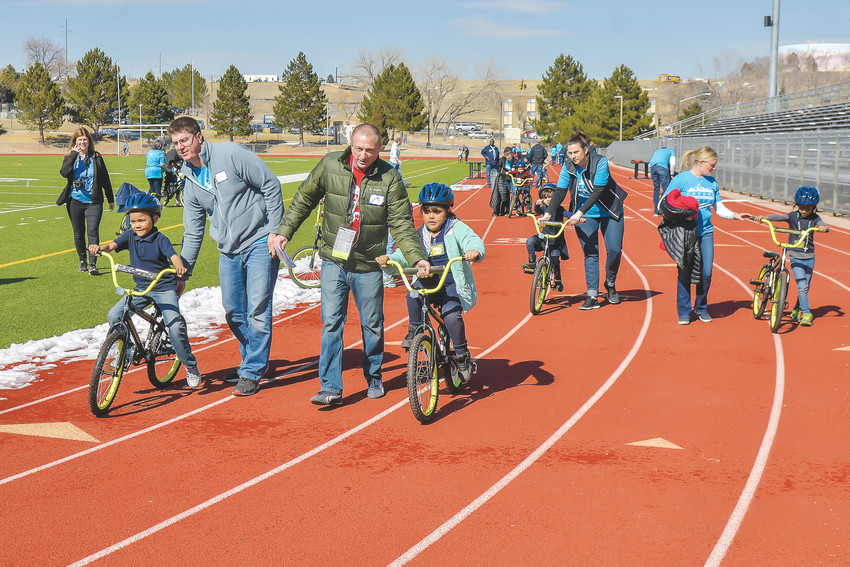 Volunteers help  students take their new wheels for a ride March 1 at the Wish for Wheels event.