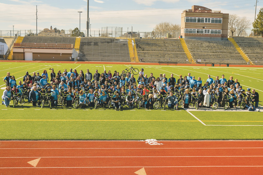 Thornton kindergartner students and the volunteers who helped them assemble their bikes and learn to uses them gather for a group shot March 1 at the Adams 12 Five Star Stadum.
