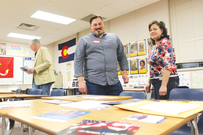 Precinct Captains Jeff and Meredith Rudolph distribute literature and answer questions at the caucus at Chaparral High School.